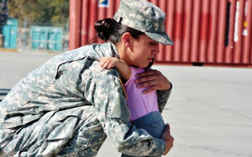 an image of a female soldier in Army fatigues crouching down to hug a small toddler baby