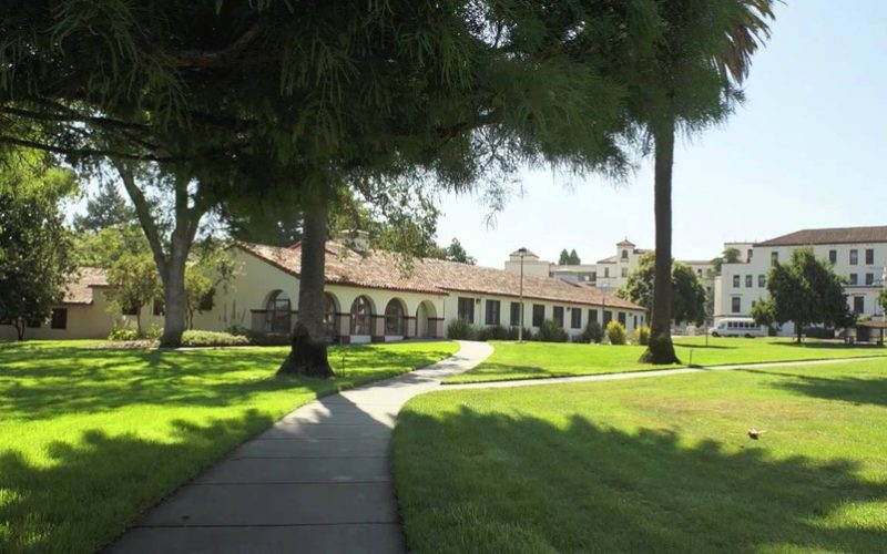 a wide angle photograph of the Yountville veterans home with a large field of grass in the foreground